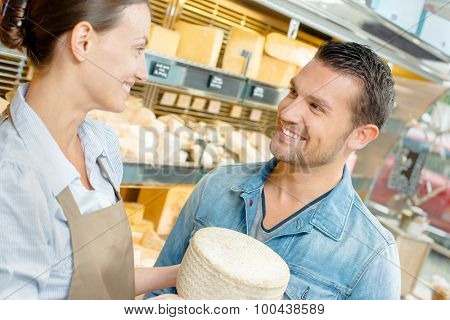 Shop assistant serving cheese