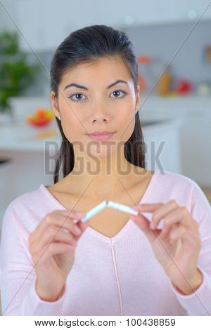 Brunette woman snapping a cigarette