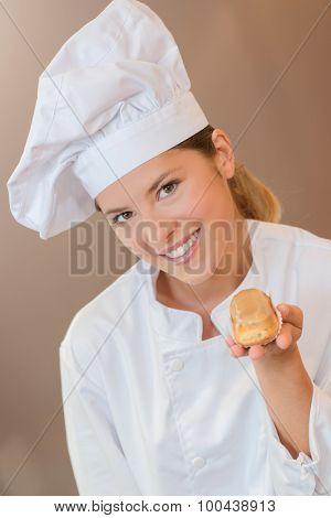 Female baker holding an eclair