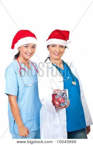 Happy Doctors Women Giving Christmas Gift