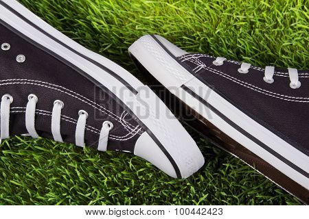 Pair Of Black Sneakers On The Green Grass