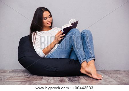 Beautiful woman sitting on the bag chair and reading book on gray background