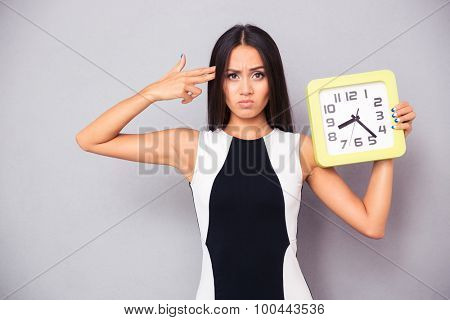 Tired woman holding clock and showing gun gesture to her head over gray background