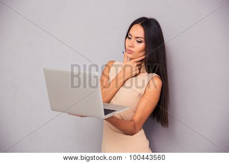 Portrait of a young elegant woman standing with laptop on gray background