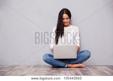 Portrait of a happy casual woman sitting on the floor with laptop on gray background