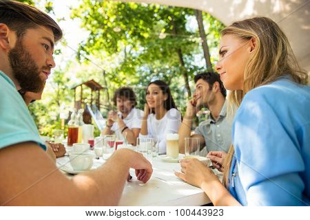 Group of a happy friends sitting at the table in outdoor restaurant