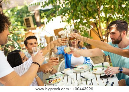 Group of a friends making toast around table at dinner party in outdoor restaurant