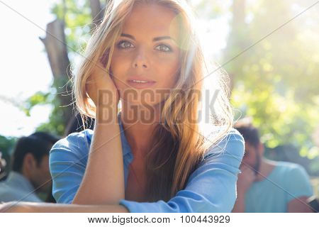 Portrait of a pretty woman with friends on background outdoors