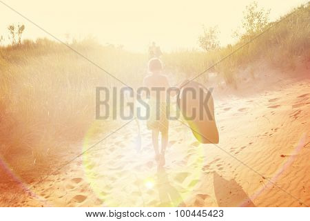 Boy carrying sleds up a beachside dune path