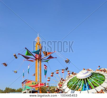 Blurred background image of  rides at a county fair with copy space.