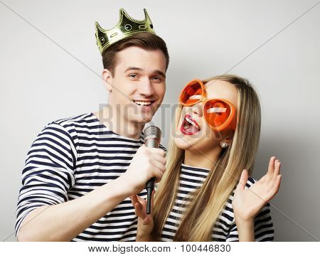 people, friendship, love and leisure concept - beautiful young loving couple with microphone. Big orange glasses and crown. Ready for party.