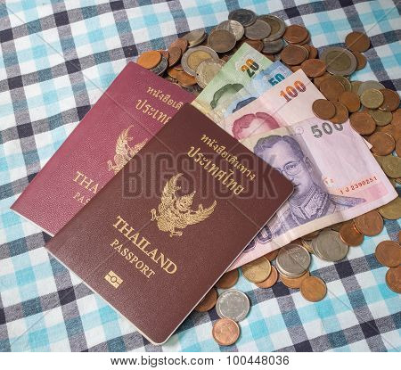 Passport And Banknotes Of Thailand Currency On The Pile Of Coins Baht Currency, On The Loincloth Sil