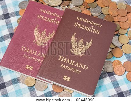 Passport Of Thailand  On The Pile Of Coins Baht Currency, On The Loincloth Silk Background.
