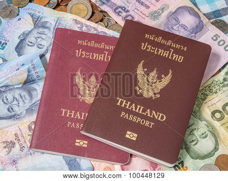 Passport Of Thailand On The Pile Of Coins And Banknotes Baht Currency.