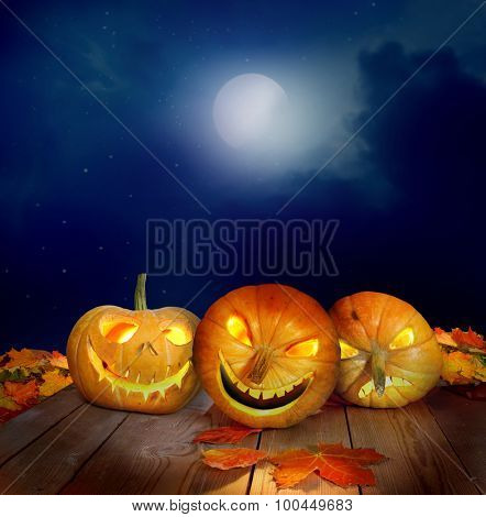 Scary halloween pumpkins on a wooden table