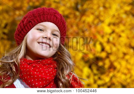 attractive young caucasian little girl in warm red colorful clothing  on yellow leaves outdoors smiling happy child kid walk