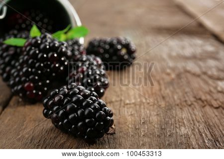 Ripe blackberries with green leaves on wooden table, closeup