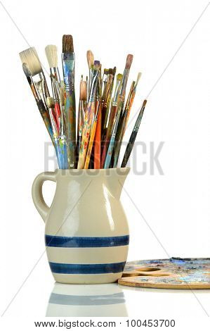 Artist paintbrushes in a jar with palette on reflective table isolated over white background