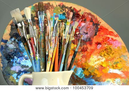 Paintbrushes and palette over gray background