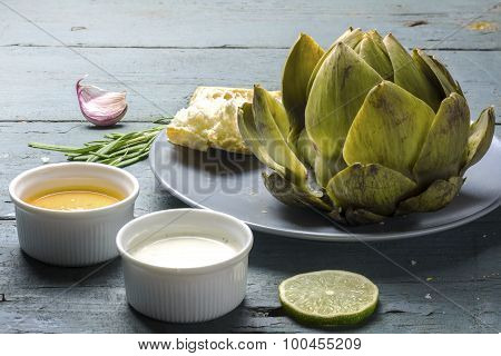 Cooked Artichoke With Dips And Bread On Rustic Gray Blue Wood