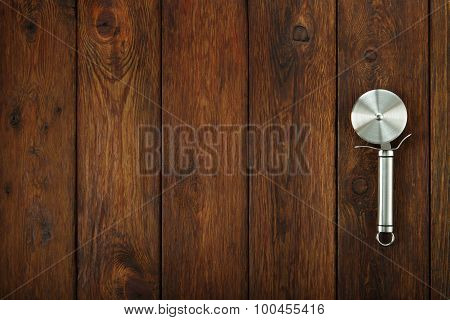 Steel Pizza Cutter At Wooden Background