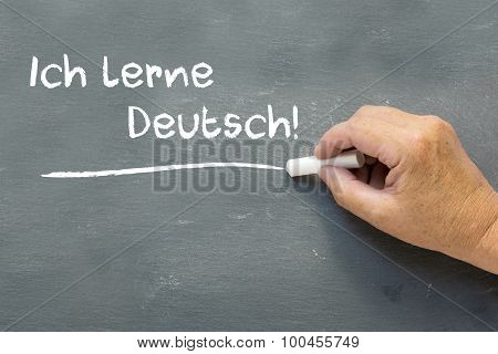 Hand On A Chalkboard With The German Words Ich Lerne Deutsch (i Learn German)