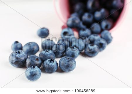 Tasty ripe blueberries in bucket on table close up