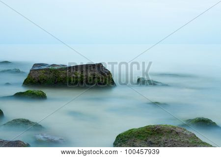 Seashore with rocks on time exposure, fogy water