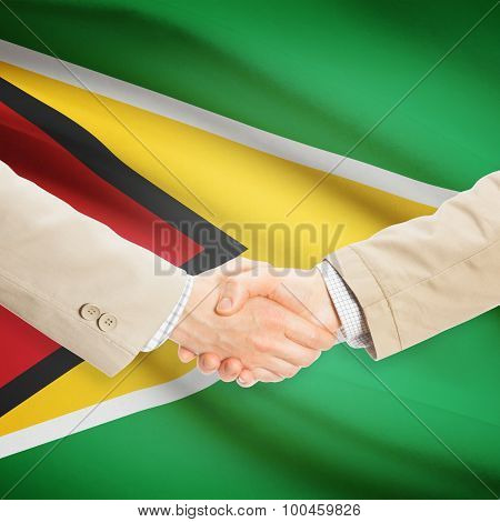 Businessmen Handshake With Flag On Background - Guyana