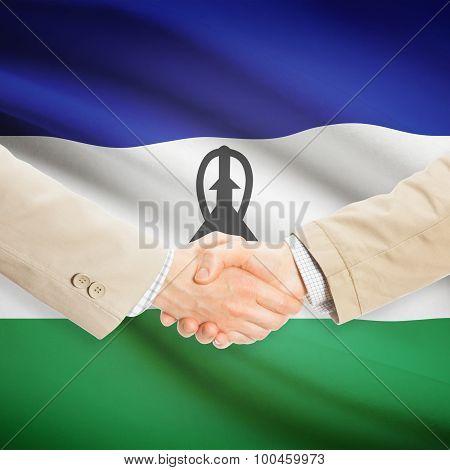 Businessmen Handshake With Flag On Background - Lesotho