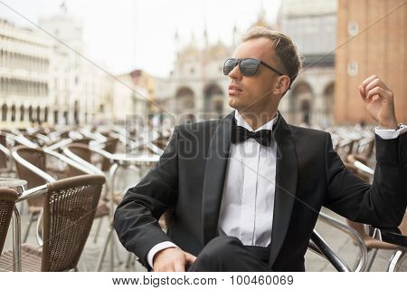 Young handsome man in tuxedo sitting in outdoor cafe