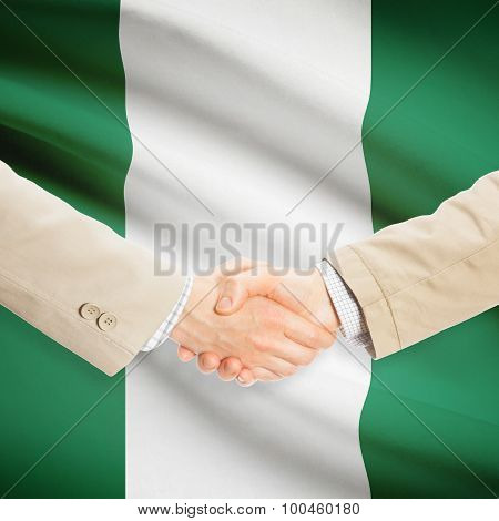 Businessmen Handshake With Flag On Background - Nigeria