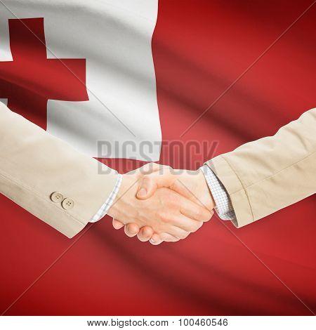 Businessmen Handshake With Flag On Background - Tonga