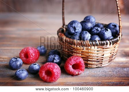 Tasty ripe berries in basket on wooden table close up