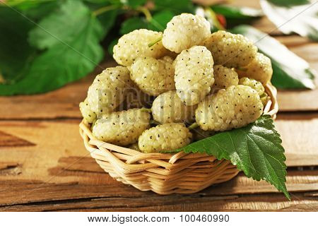 Fresh mulberry in wicker basket on wooden table, closeup