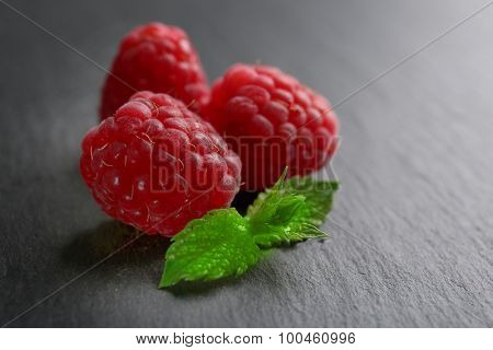 Fresh red raspberries on wooden background