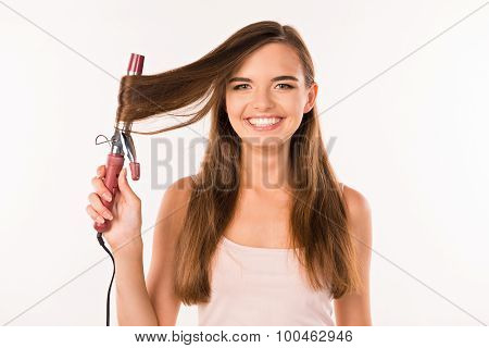 Girl With Curling. Girl Twists Hair Curling On