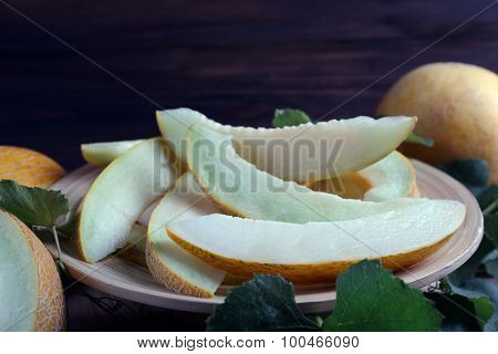 Slices of ripe melons with green leaves on table close up