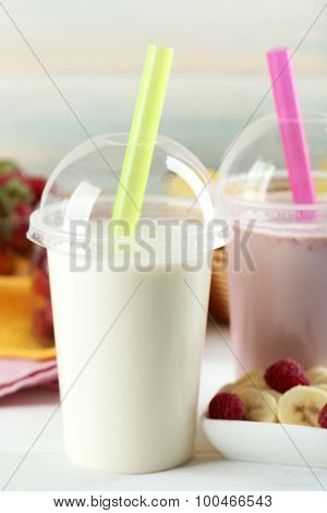 Plastic cup of milkshake on light wooden background