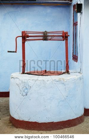 Rural water well on white wall background