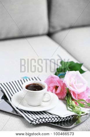 Cup of coffee with flowers on tray on sofa in room