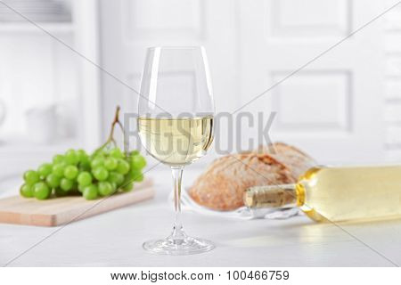Still life of wine, grape and bread on light background