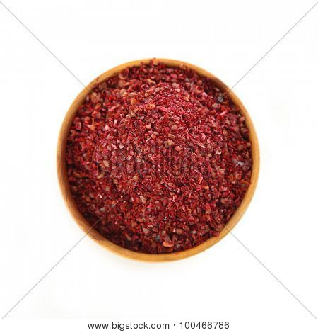 Sumac in wooden bowl, isolated on white
