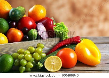 Heap of fresh fruits and vegetables in crate on wooden table close up