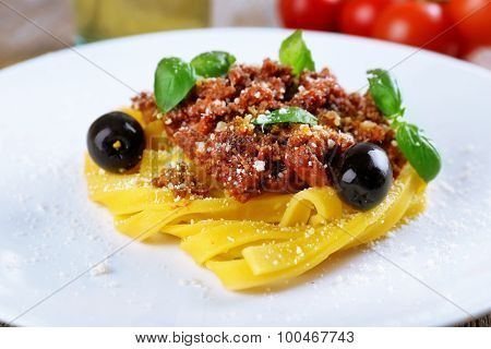 Pasta Bolognese with parmesan and basil on plate close up