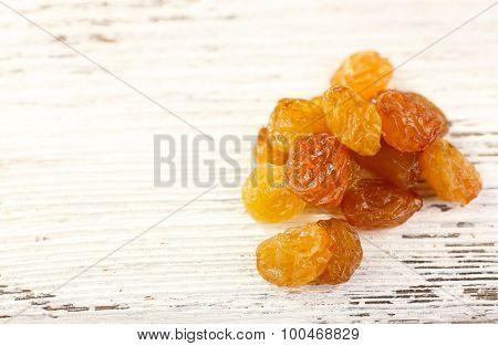 Heap of raisins on wooden background