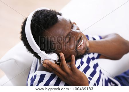 African American man with headphones on sofa in room