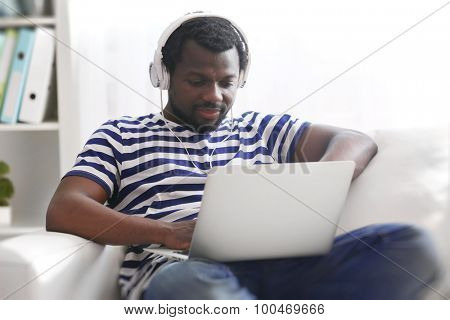 African American man listening music with headphones on sofa in room
