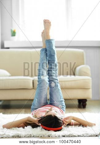 Woman listening music in headphones while lying on carpet in room