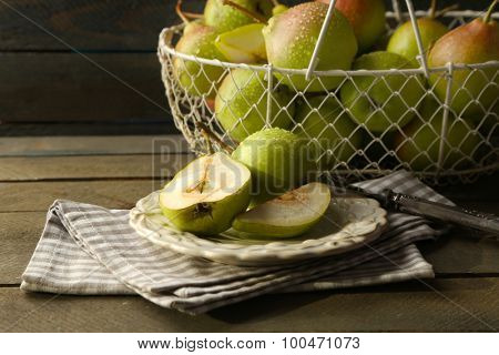 Ripe tasty pears in basket on table close up